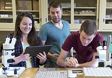 Instructor helping two students in research lab